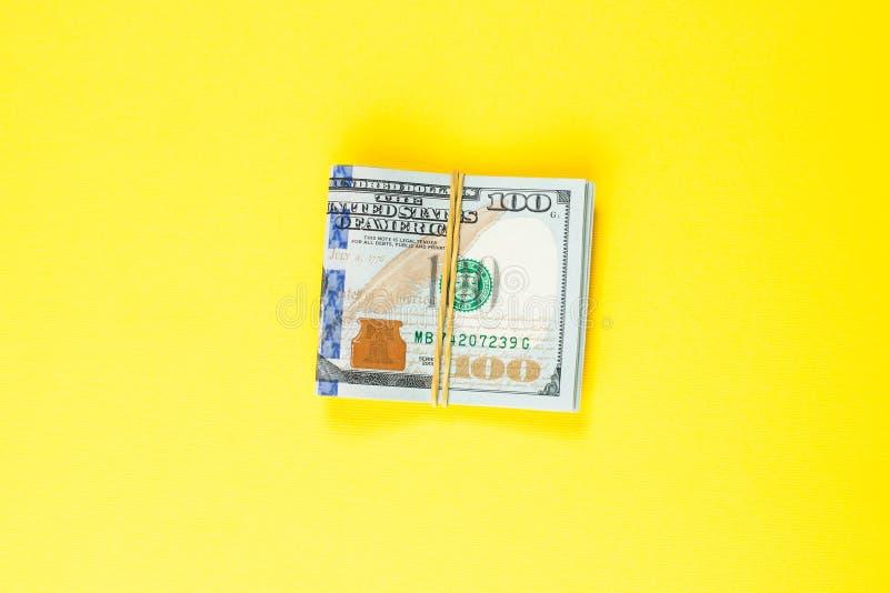 Efectivo del dinero del dólar americano en fondo amarillo Dólares americanos 100 de billete de banco imágenes de archivo libres de regalías