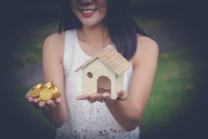 Efectivo del dinero y un hogar modelo en manos de la mujer foto de archivo