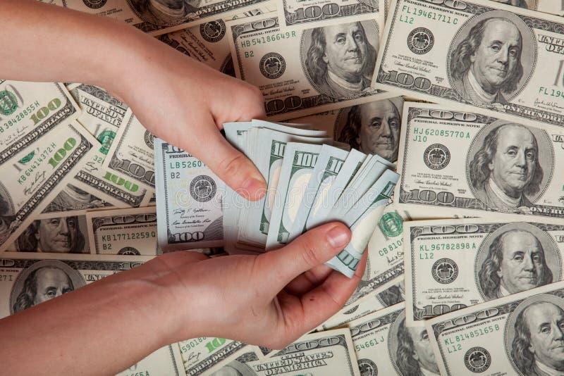 Efectivo disponible Beneficio, ahorros Pila de dólares una persona que está contando el dinero contra la perspectiva del dinero,  imagen de archivo