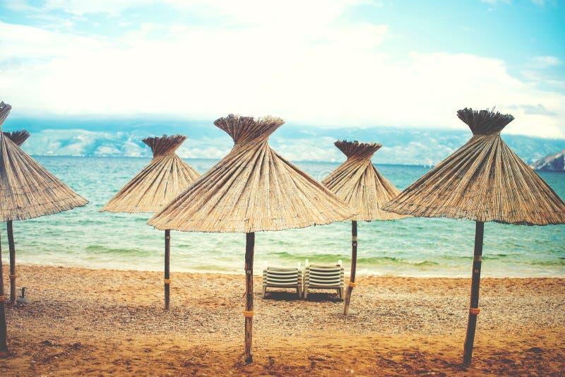 Efecto retro de Instragram sobre la foto, parasoles de playa con la paja fotos de archivo