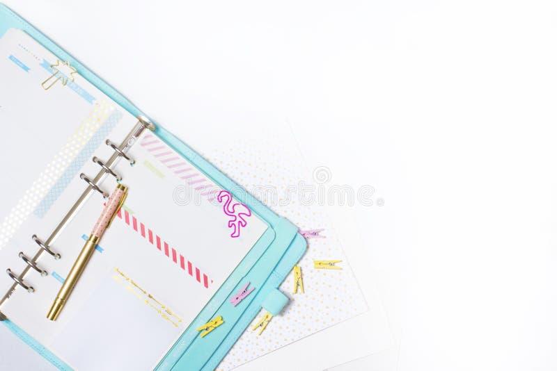 Efectos de escritorio femeninos: la carpeta de papel colorida acorta la palma y el flamin foto de archivo