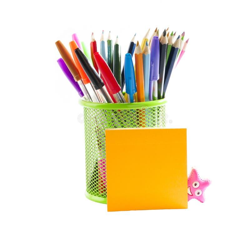 Efectos de escritorio. Lápices coloreados en un soporte del lápiz y notas del palillo imagen de archivo libre de regalías