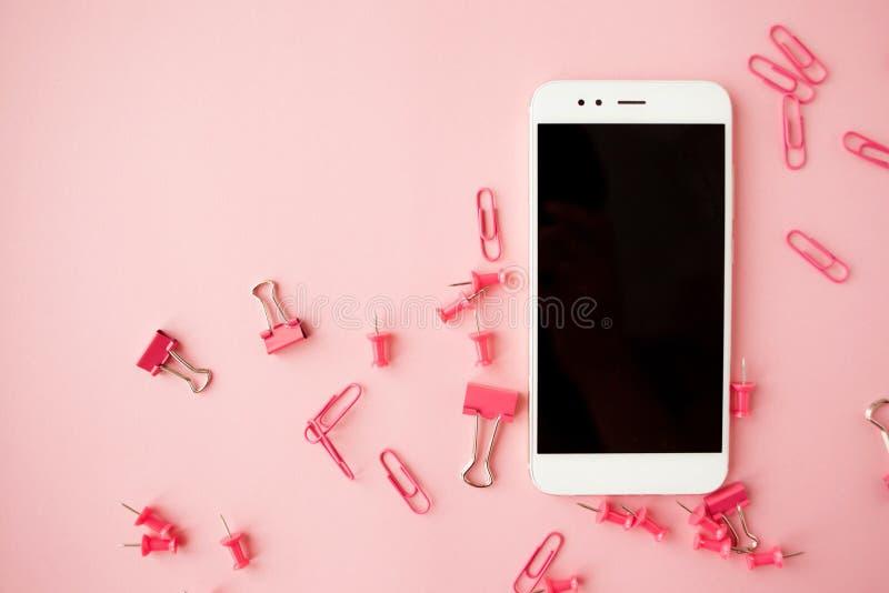 Efectos de escritorio rosados rotos, smartphone blanco, fondo rosado flatlay imagen de archivo libre de regalías