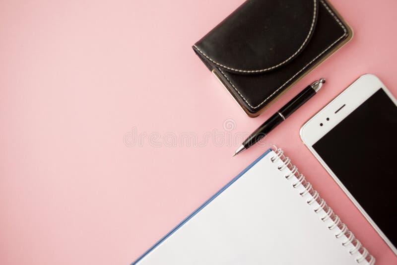 Efectos de escritorio, smartphone blanco, pluma, cartera, reloj, calendario, cuaderno Fondo rosado imagen de archivo libre de regalías