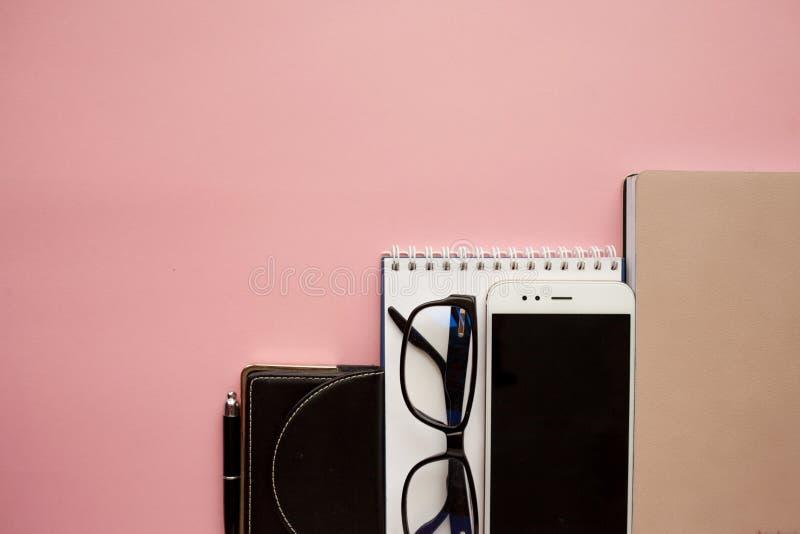 Efectos de escritorio, smartphone blanco, vidrios, pluma, cartera, reloj, calendario, cuaderno Fondo rosado fotografía de archivo