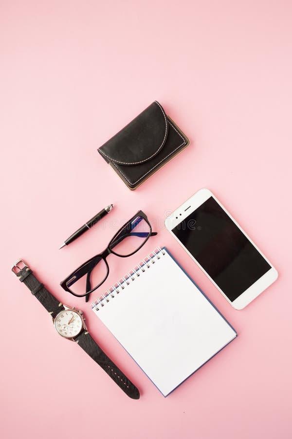 Efectos de escritorio, smartphone blanco, vidrios, pluma, cartera, reloj, calendario, cuaderno Fondo rosado foto de archivo