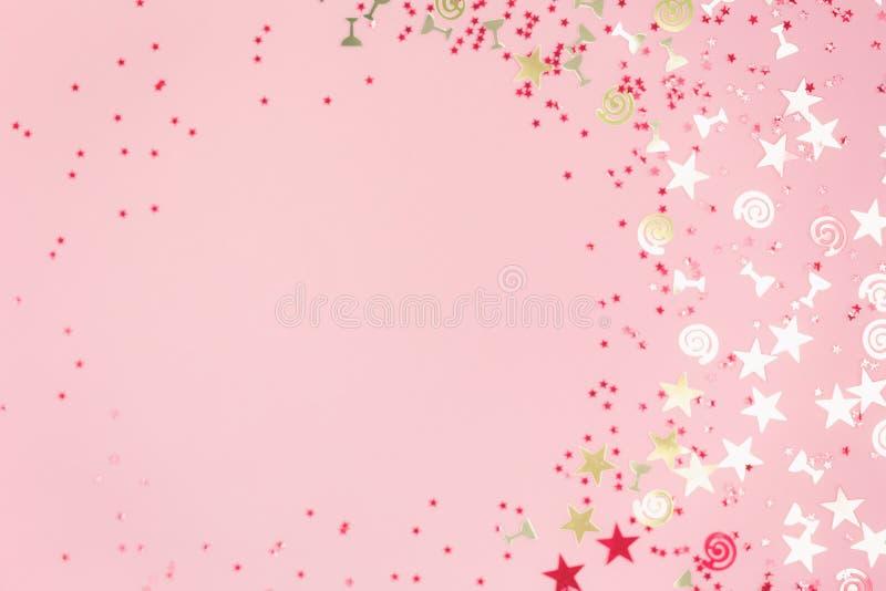 A efervesc?ncia dourada classificou confetes festivos no rosa fotos de stock