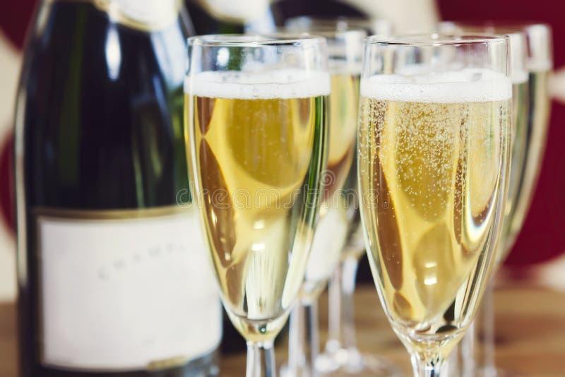 Efervescendo o champanhe em flautas de champanhe imagens de stock