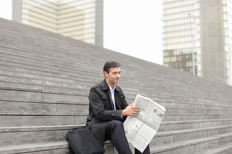 male business tutor sitting on stairs and reading newspaper royalty free stock image