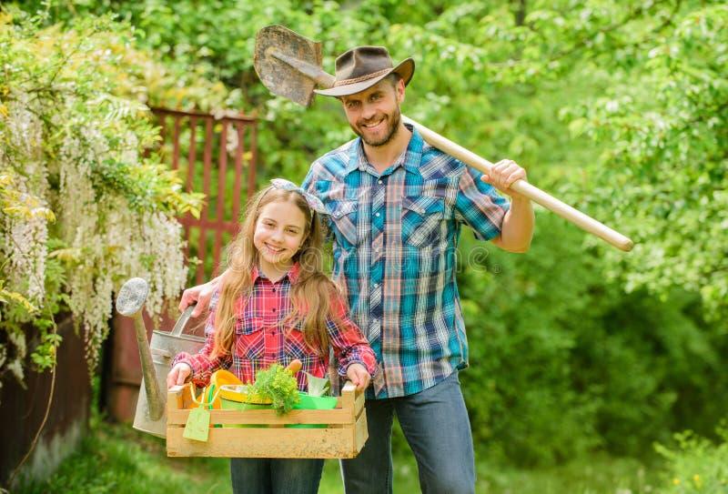 Effectu? avec amour fille et père sur le ranch pays de village de ressort ?cologie Outils de jardinage neufs, plateau de canne pe photos stock