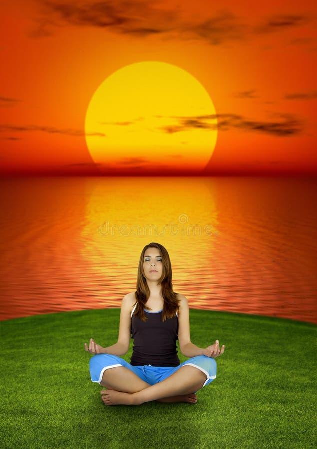 Effectuer le yoga au coucher du soleil image libre de droits