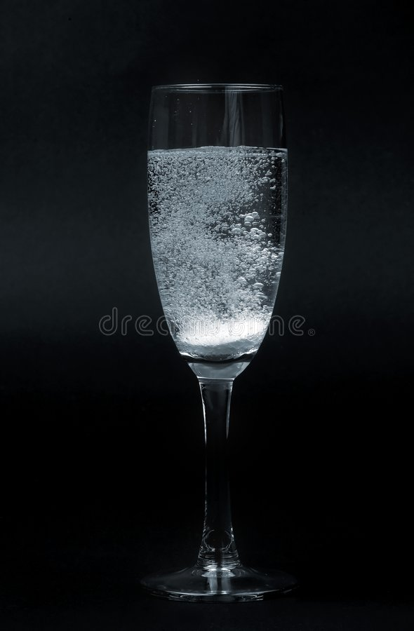 Effervescent pill in glass. Isolated on black background stock photos