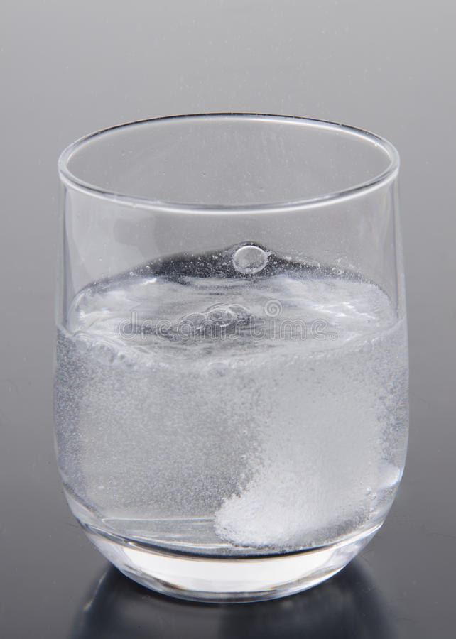 Effervescent tablet in a glass of water stock image
