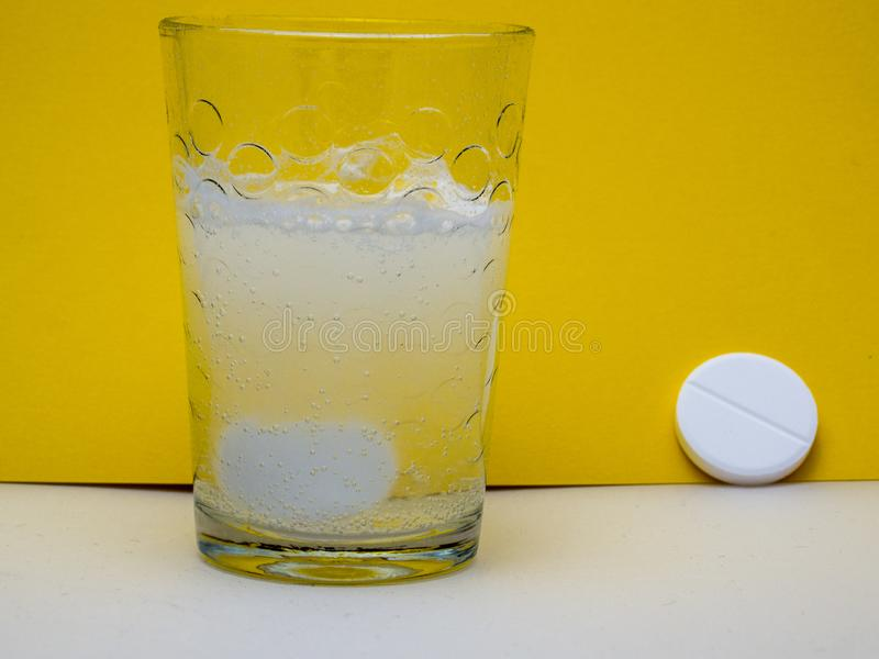 Effervescent tablet in water. Effervescent tablet in a glass of water on a yellow background royalty free stock photo