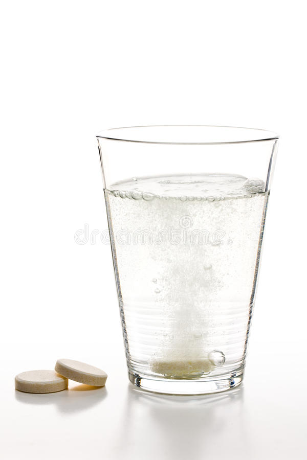 Effervescent tablets and glass with water. The effervescent tablets and glass with water royalty free stock photo