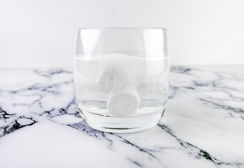 Effervescent tablets in glass with water. Fast dissolving medicine in glass on white marble background.  royalty free stock image