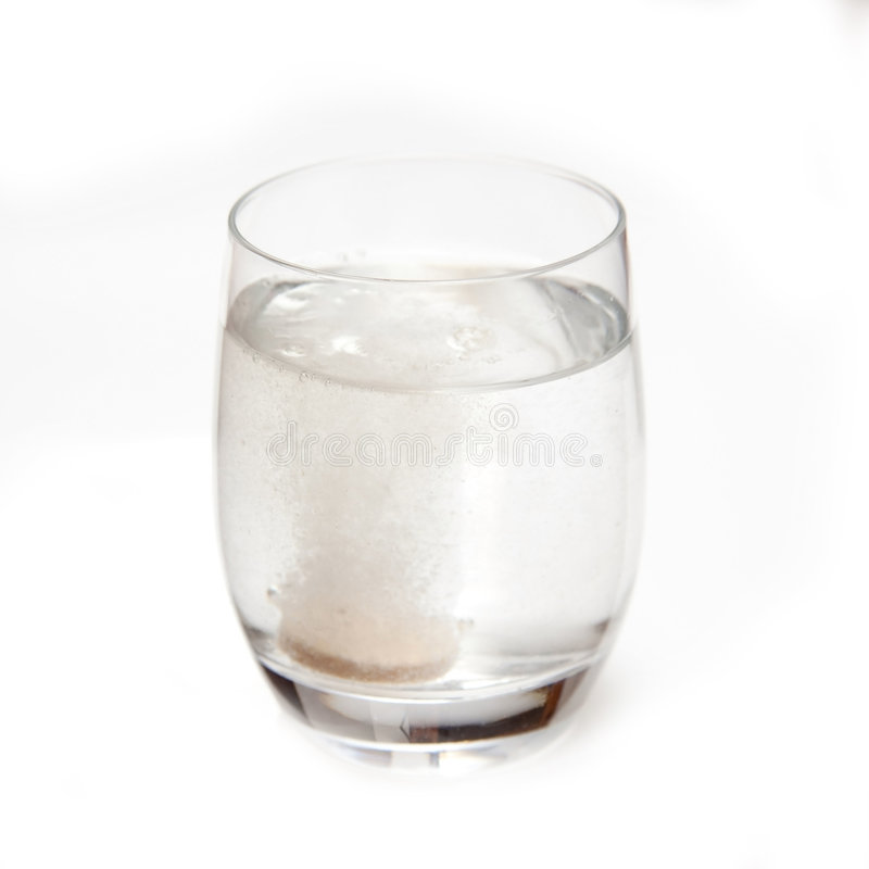 Effervescent Vitamin C. Tablet bubbling in a glass of water. Isolated on a white background royalty free stock photo