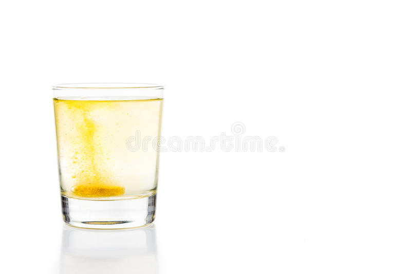 Effervescent vitamin C tablet bubbles in glass of water.  royalty free stock photo