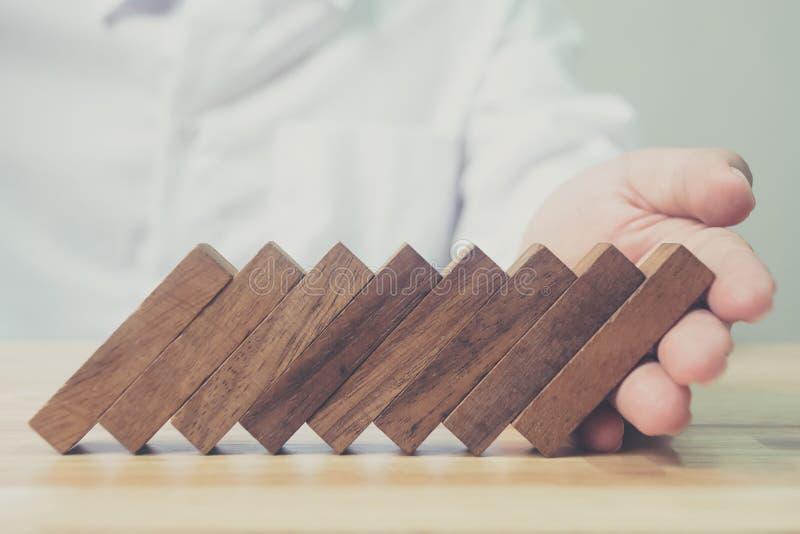 Effetto di domino del blocchetto di legno di sostegno della mano dell'uomo d'affari, rischio d'impresa immagini stock