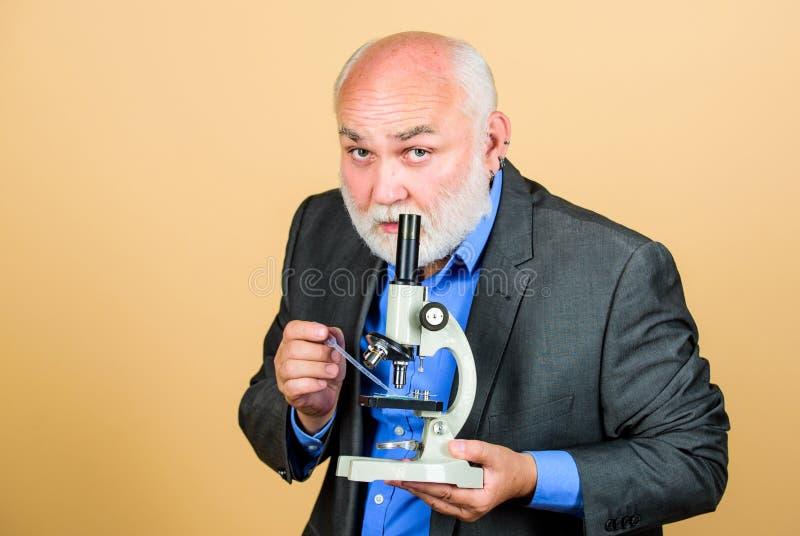 Effettuare ricerca chimica nel laboratorio della scuola insegnante barbuto maturo con il microscopio università del biologo dell' immagini stock