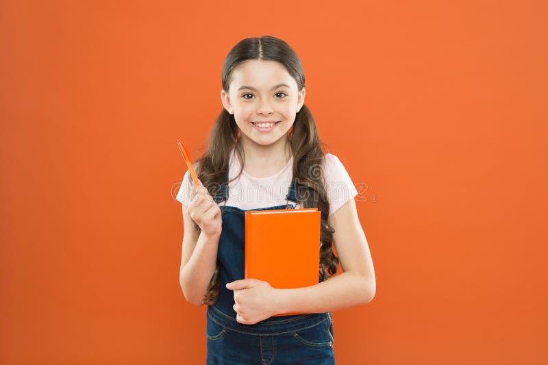 Effettuare ricerca lezione della letteratura Di nuovo al banco Bambina felice con il taccuino la ragazza della scuola ha letto il fotografie stock libere da diritti