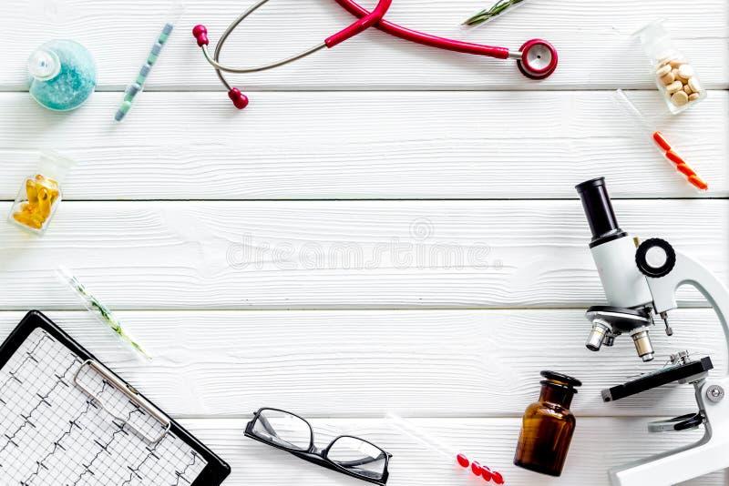 Effettui la ricerca medica con il microscopio, lo stetoscopio, il cuscinetto, le pillole e la provetta su derisione di legno bian immagini stock