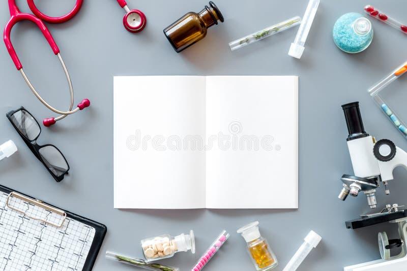 Effettui la ricerca medica con il microscopio, lo stetoscopio, i prova-tubi, taccuino in laboratorio sul modello grigio di vista  fotografia stock