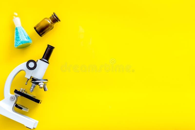 Effettui la ricerca medica con il microscopio, prova-tubi in laboratorio sul modello giallo di vista superiore del fondo immagine stock libera da diritti