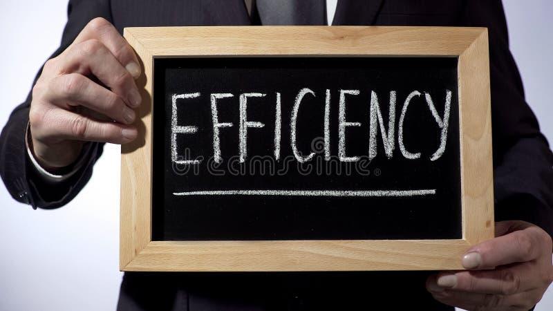 Efficiency written on blackboard, male in black suit holding sign, business royalty free stock photo