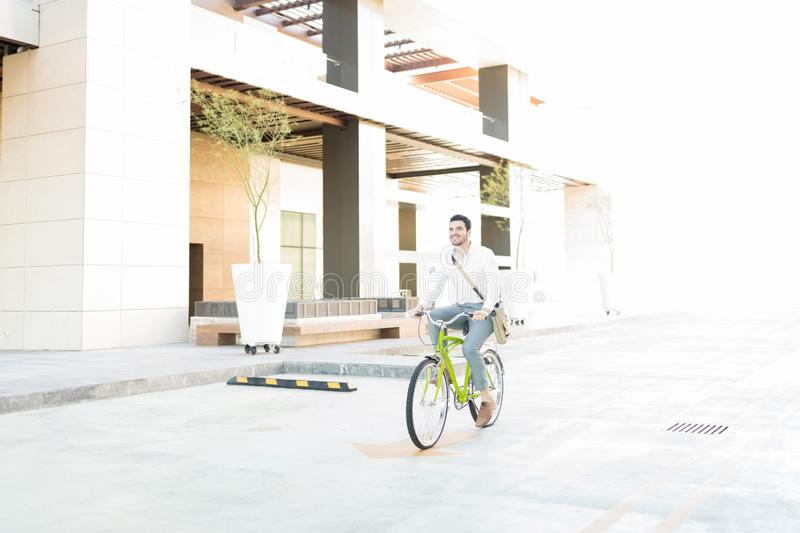 Bicycle Commuting Contributes To Clean Environment. Efficient young businessman commuting on bicycle in city royalty free stock photo