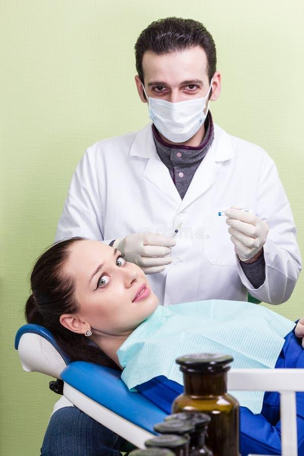 Effrayé patient l'injection de dentiste photos stock