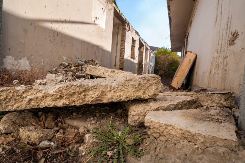 Efterdyning återstår av orkan- eller jordskalvkatastrofskada på förstört gammalt hus med kollapsad selektiv foc för tak- och tege royaltyfria bilder