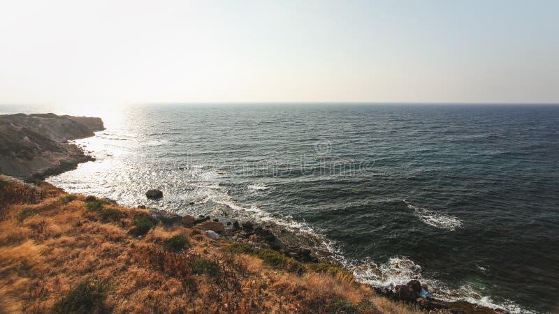 Eftermiddagsolen skiner på grov kust med steniga klippor och det djupa havet i den Karpass regionen av nordliga Cypern royaltyfri foto