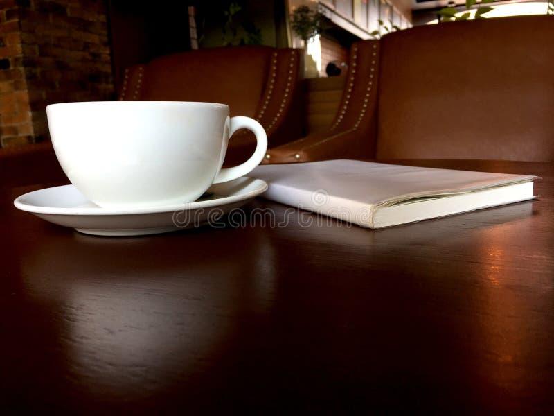 Eftermiddagte i den vita koppen med anteckningsboken på den bruna trätabellen royaltyfri fotografi