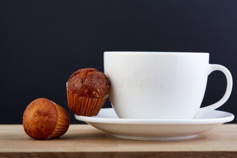 Eftermiddagte och muffin på portiontabellen över mörk grå bakgrund, närbild, selektiv fokus royaltyfri foto