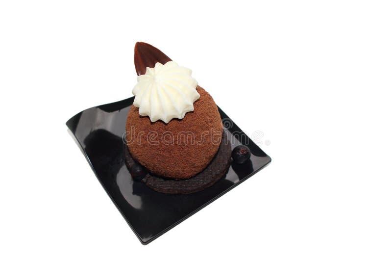 Efterrätt för chokladsfärkaka på ljusbrun grund med chokladganache och vit chokladbladgarnering arkivbilder