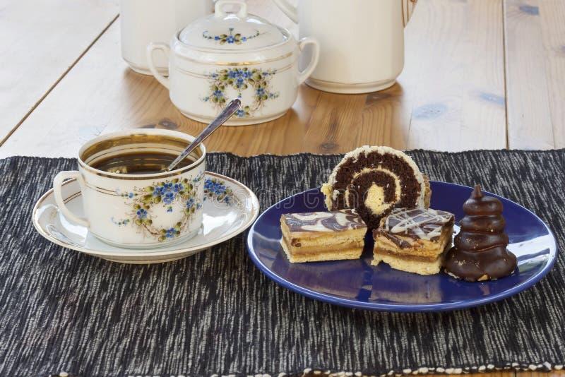 Efterrätt med kaffe, chokladkakor och rullar på tabellen, royaltyfria bilder
