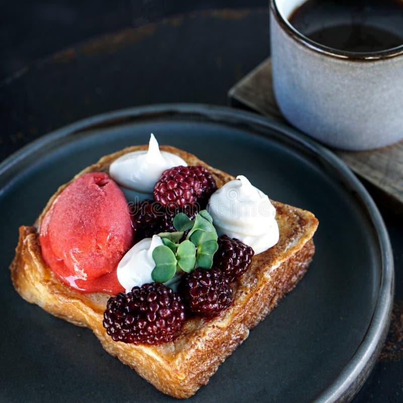 Efterrätt med kräm och bär på den mörka plattan och koppen av americanokaffe royaltyfri foto