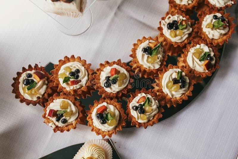 Efterrätter med frukter, muffin på ställning, bästa sikt, den moderna söta tabellen på bröllop eller baby shower Lyxigt sköta om  arkivbilder