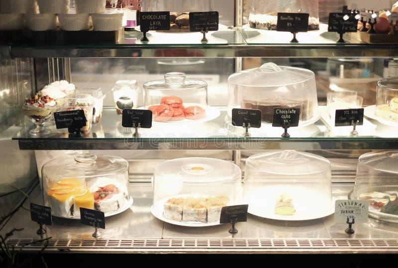 Efterrätter på försäljning med namn och priser i bageri shoppar royaltyfri fotografi