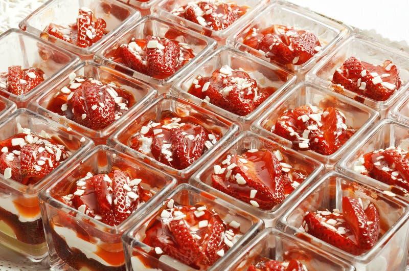 Efterrättjordgubbar in i små fyrkantiga exponeringsglas royaltyfri foto