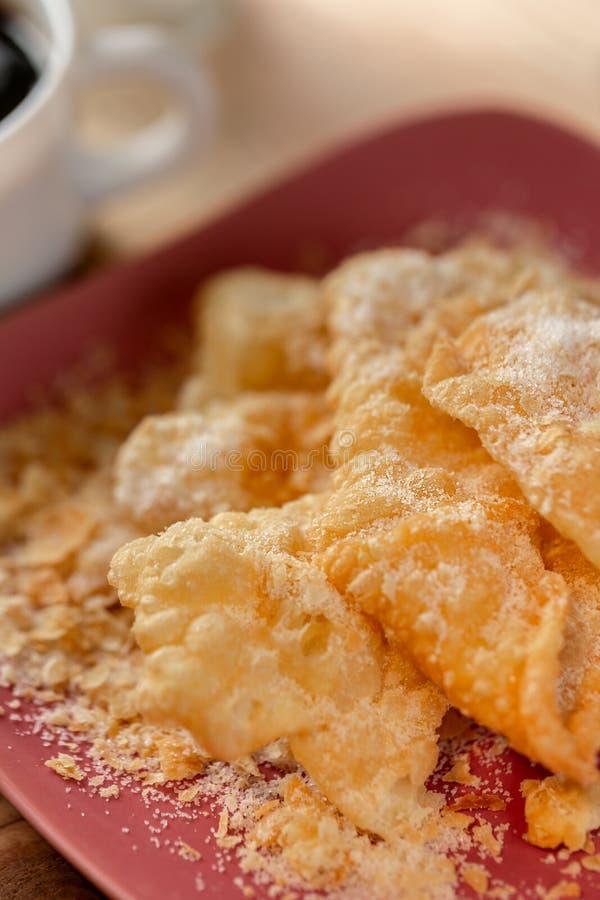 Efterr?tt Knastrade frasiga kakor med socker p? en platta och en kopp kaffe p? en tr?tabell royaltyfria foton
