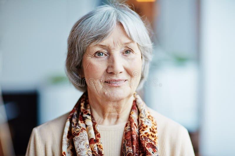 Eftertänksam äldre kvinna vid fönstret royaltyfri fotografi