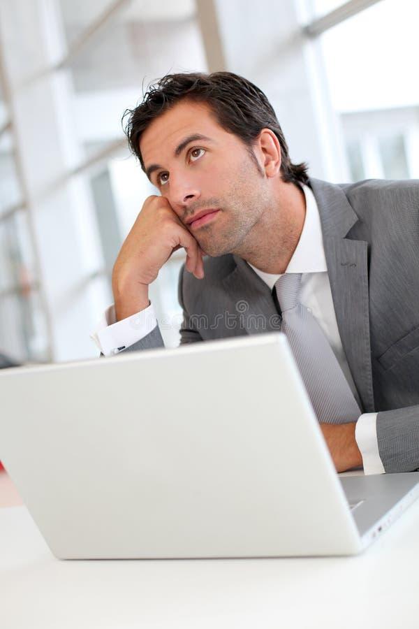 Eftertänksam affärsman med bärbara datorn royaltyfri fotografi