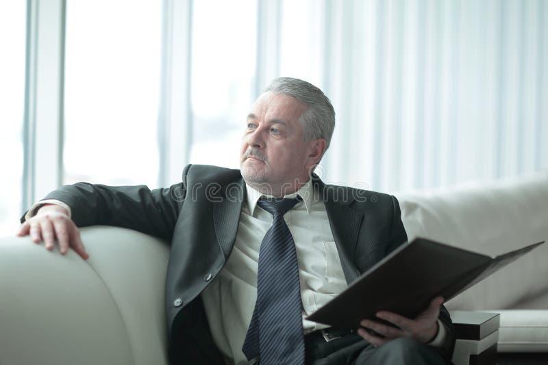 Eftertänksam affärsman med skrivplattasammanträde på kontorssoffan royaltyfria bilder