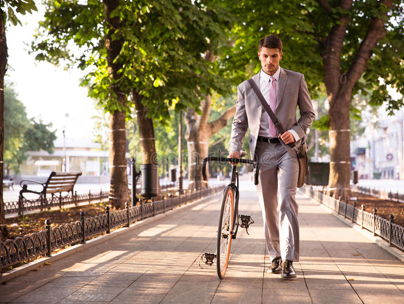 Eftertänksam affärsman som går med cykeln fotografering för bildbyråer