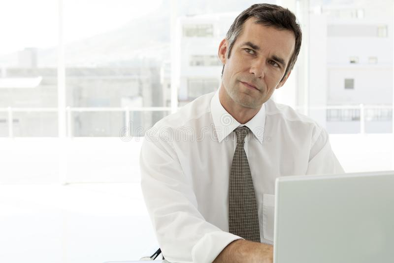 Eftertänksam affärsman som i regeringsställning arbetar på bärbara datorn royaltyfria foton