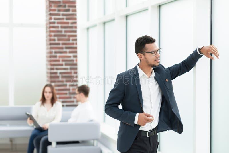 Eftertänksam affärsman som ser till och med ett stort kontorsfönster arkivfoton