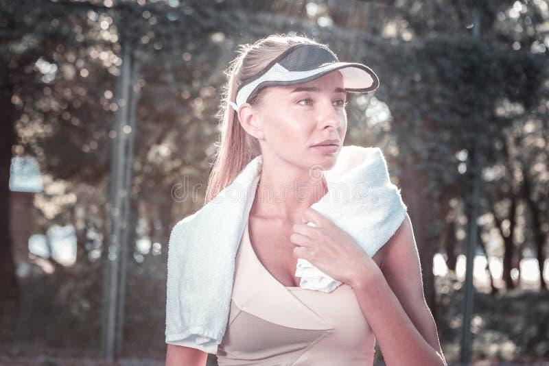 Eftertänksam angenäm kvinnlig spelare som vilar efter tennis royaltyfri foto