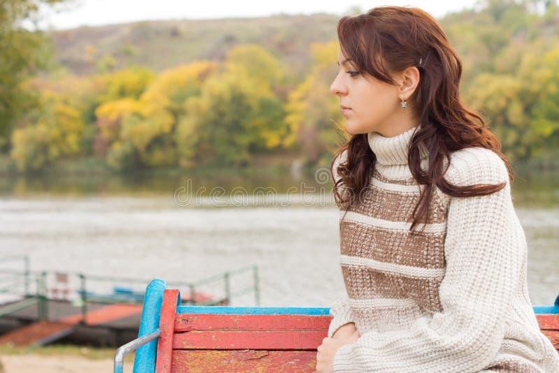 Eftertänksam attraktiv ung kvinna utomhus arkivbild